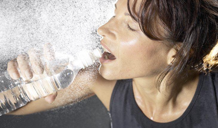 Imagem de uma mulher bebendo água corrida