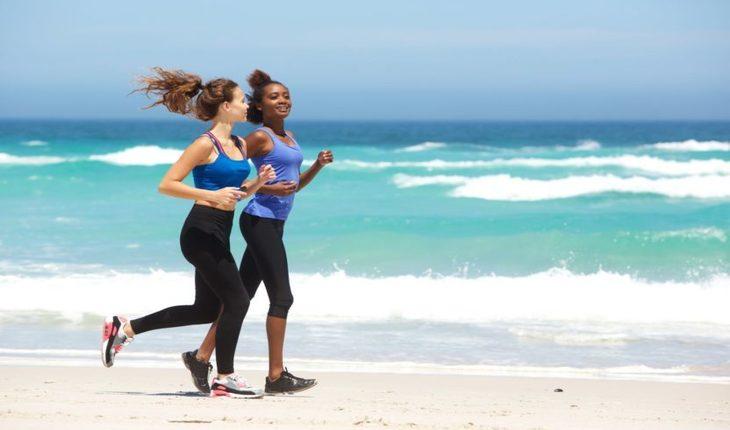 Imagem duas mulheres correndo na pria dia ensolarado. Corrida