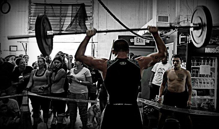 Atleta levantando uma barra com pesos, sendo observado por outras pessoas