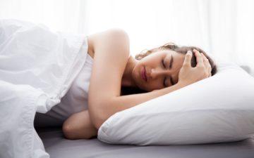 mulher deitada com enxaqueca