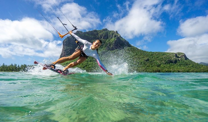 Mulher praticando kitesurf, passando a mão na água