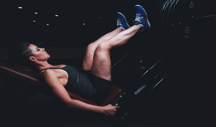 mulher executando o exercício na máquina de leg press
