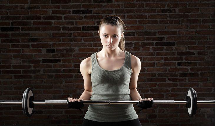 mulher realizando exercício de levantamento com a barra