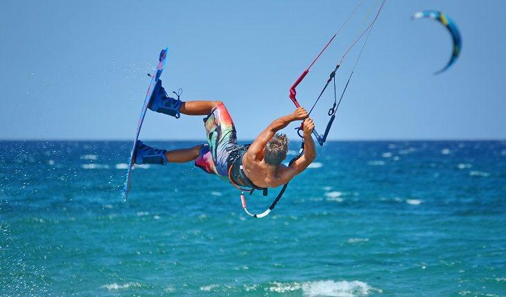 Homem realizando uma manobra de kitesurf