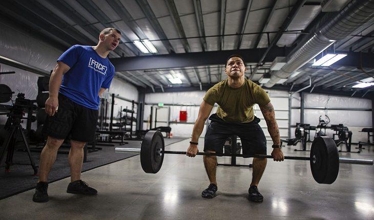 Personal auxiliando aluno em aula de CrossFit