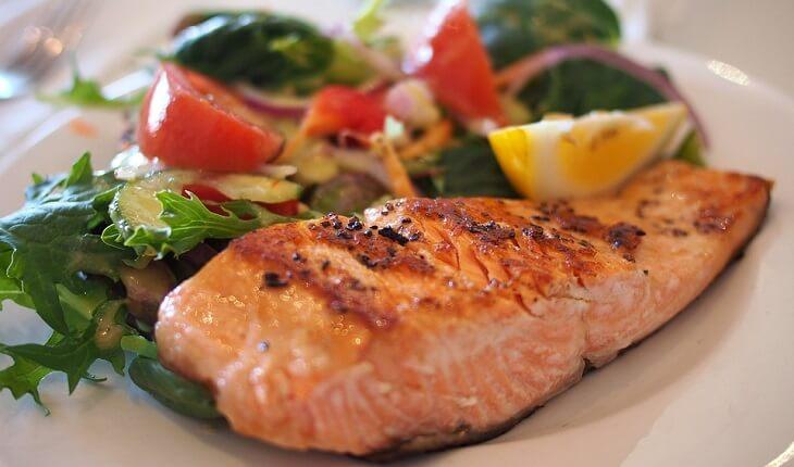 Na foto, um prato de salmão com salada. Nutrição esportiva