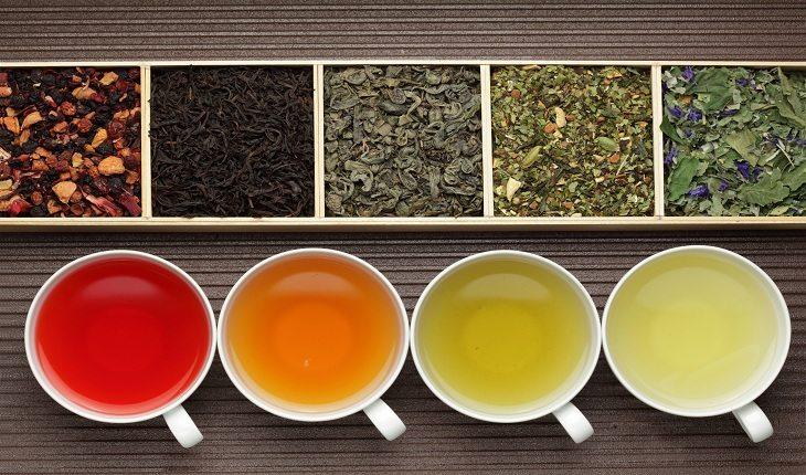 cinco recipientes colocados em frente a cinco xícaras de chá