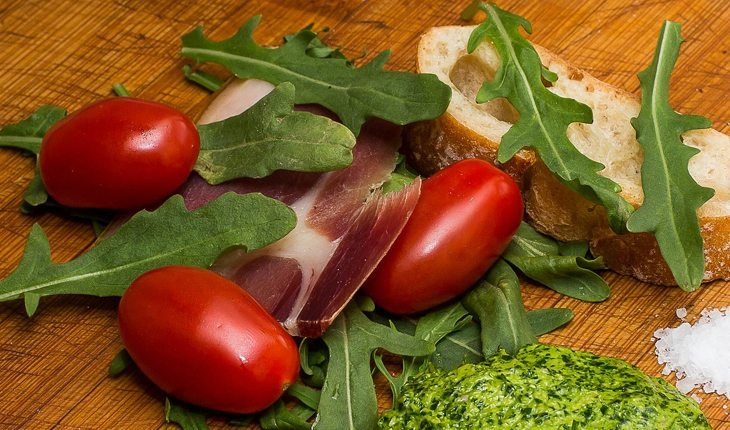 foto de rúculas em uma tábua junto de tomates