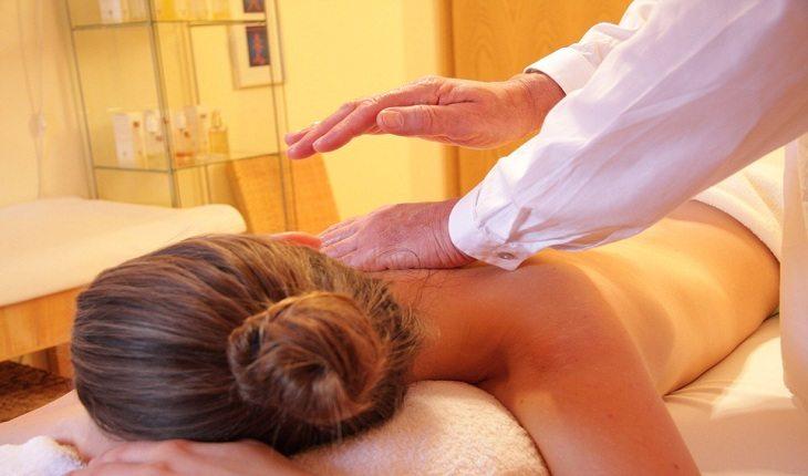mulher deitada recebendo massagem em um consultório