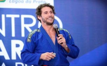 Foto de Flávio Canto de kimono, com o microfone na mão, durante uma palestra