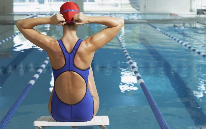 mulher sentada em um trampolim de uma piscina, prestes a entrar para praticar pilates na água