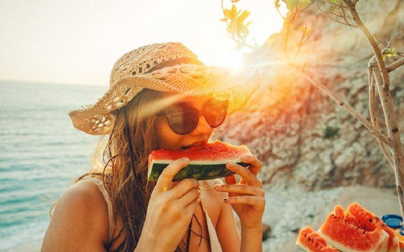 Mulher comendo melancia ao por do sol Boa alimentação no verão