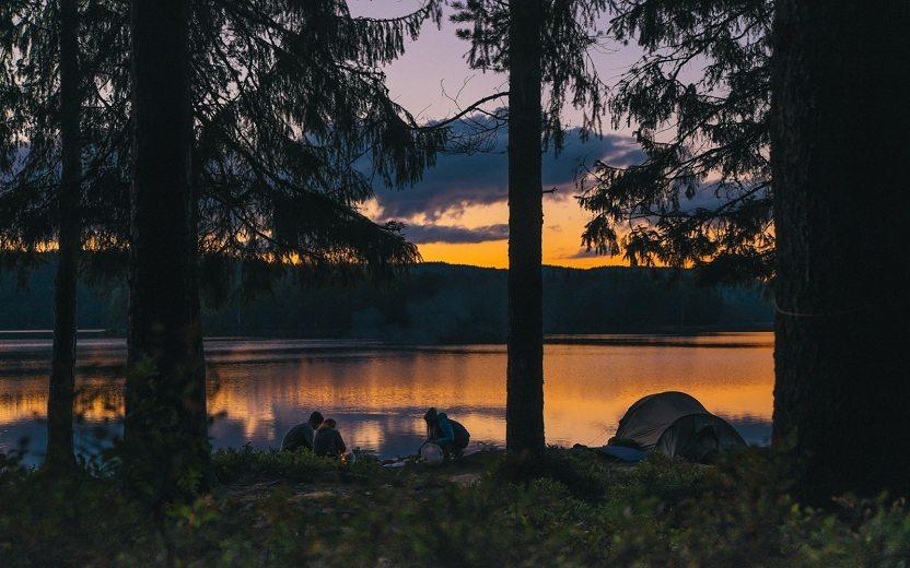 amigos acampando perto de um lago acampar pela primeira vez