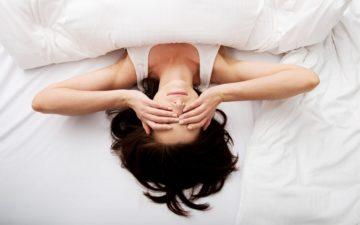 Mulher deitada em cama com mãos no rosto evitar antes de dormir