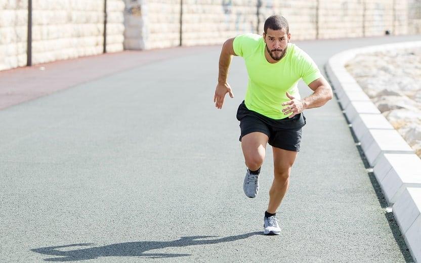 Fortalecimento muscular para corrida. Na foto, um corredor na rua, com semblante de esforço