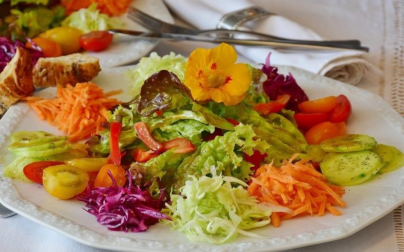 Prato de salada sob a mesa. Saladas que valem por uma refeição