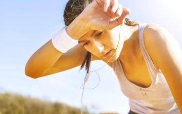 mulher treinando em altas temperaturas, cansada e limpando o suor