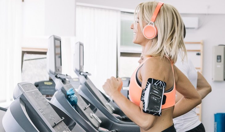 Exercícios físicos e câncer de mama. Na foto, uma mulher loira com o cabelo curto correndo na esteira