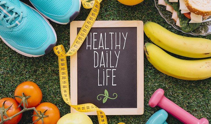 Exercícios físicos e câncer de mama. Na foto, elementos que lembram a relação entre exercícios físicos, alimentos e saúde. Pesos, frutas, tênis e etc