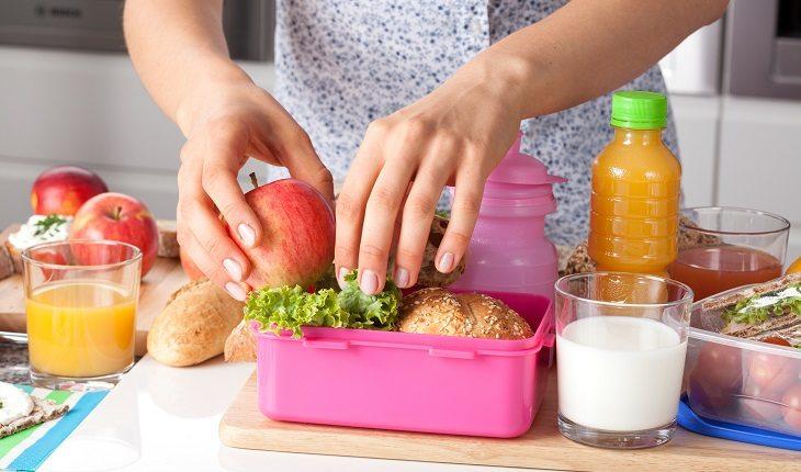 Lanches saudáveis para crianças. Pessoa preparando uma lancheira com comidas saudáveis