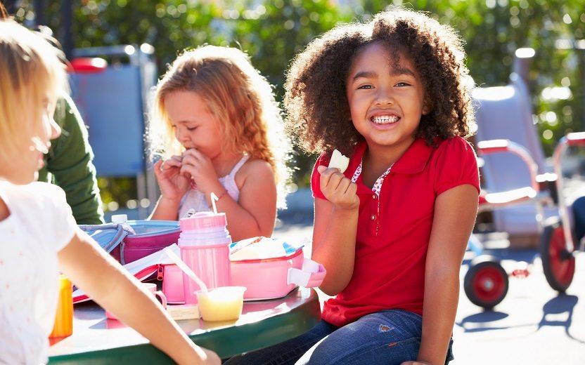 Lanches saudáveis para crianças: menina comendo feliz
