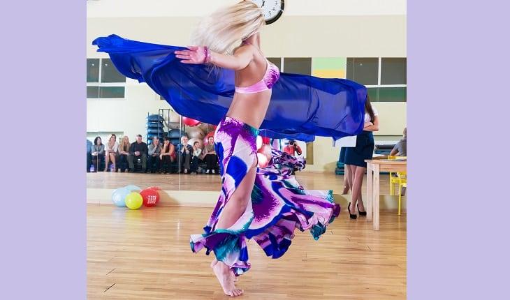 Uma mulher com as vestimentas roxas rodopia em uma aula de dança do vente