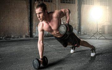 Imagem de um homem branco e forte fazendo flexões de braço com um altere em cada mão. 7 minutos