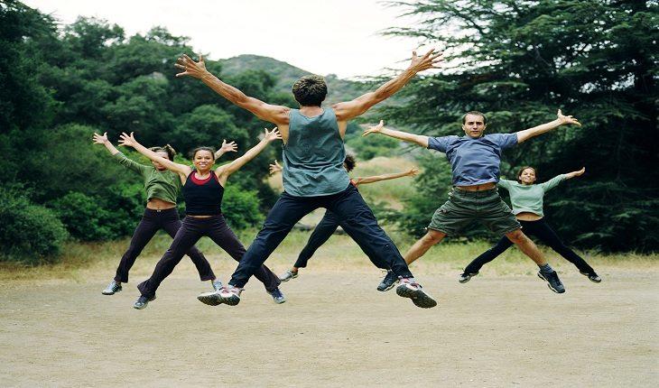 Imagem de um homem de costas para a câmera liderando um grupo de pessoas que está realizando polichinelos. 7 minutos