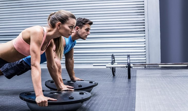 Imagem de um casal realizando o burpee com bosu em uma academia. Bosu