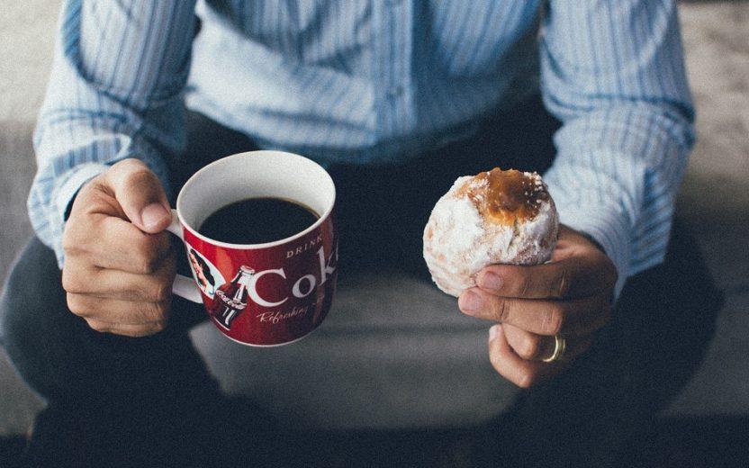 Homem sentado segurando em uma mão uma xícara de café e na outra um bolinho Fome