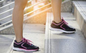 mulher fazendo alongamento em escadas com tênis lilás de corrida
