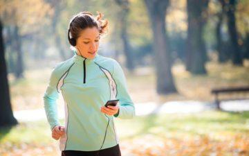 A foto mostra uma mulher correndo procurando no celular aplicativos fitness