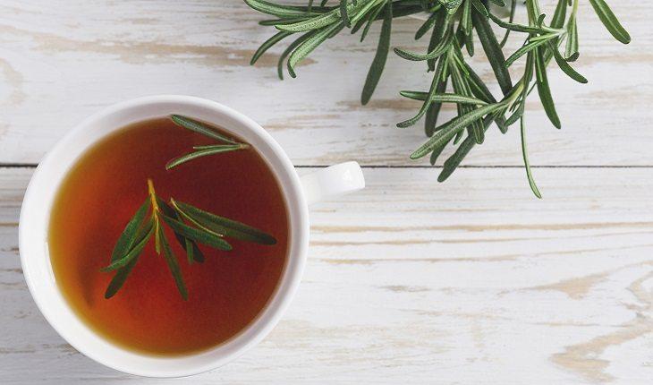 a foto mostra uma xícara com chá de alecrim, um dos alimentos antienvelhecimento, com folhas da erva em cima