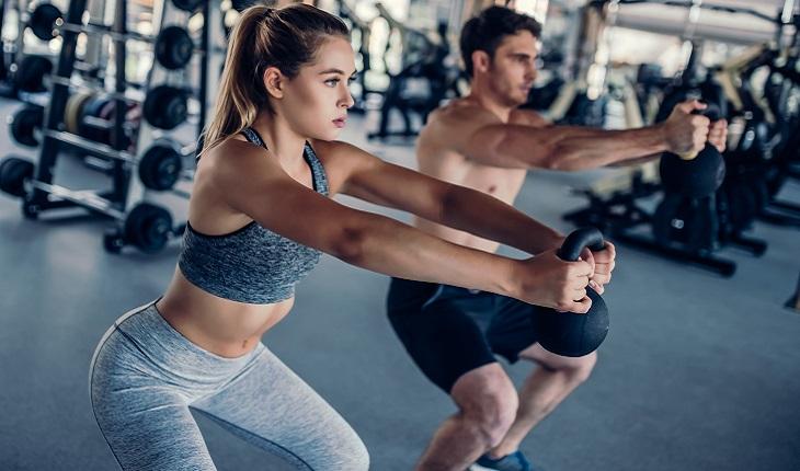 homem e mulher fazendo agachamento na academia