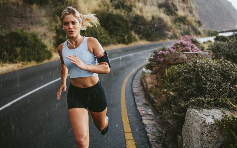 A foto mostra uma mulher correndo em uma estrada com o celular preso em seu braço esquerdo, ilustrando o uso de aplicativos para corrida