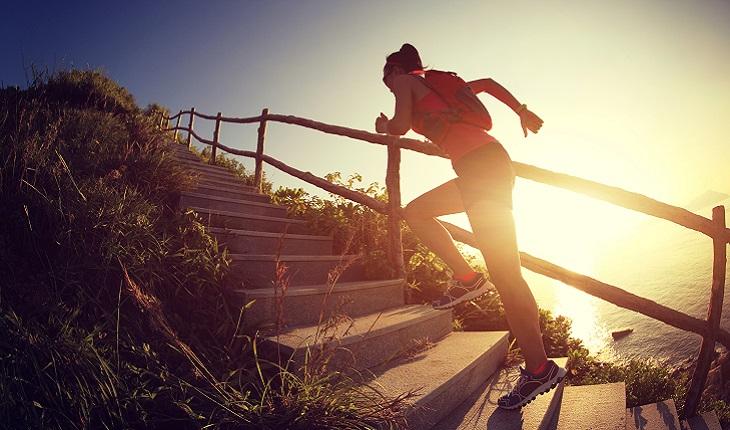 mulher correndo subindo escada na montanha