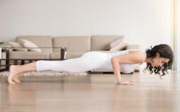 Treino de 15 minutos. Na foto, uma mulher fazendo flexão em casa.