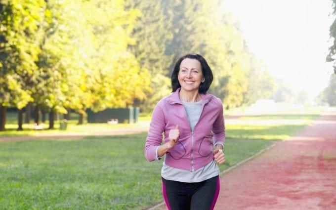 Mulher morena correndo feliz em um parque Cuidados no inverno