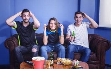 Petiscos saudáveis para os jogos da Copa. Na foto, amigos sentados em um sofá assistindo futebol.