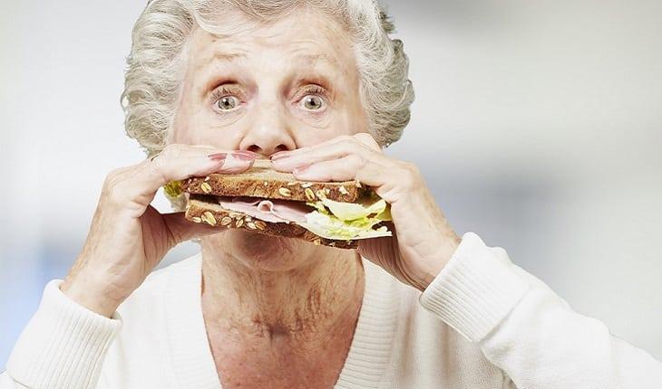 A foto mostra uma mulher idosa comendo um sanduíche