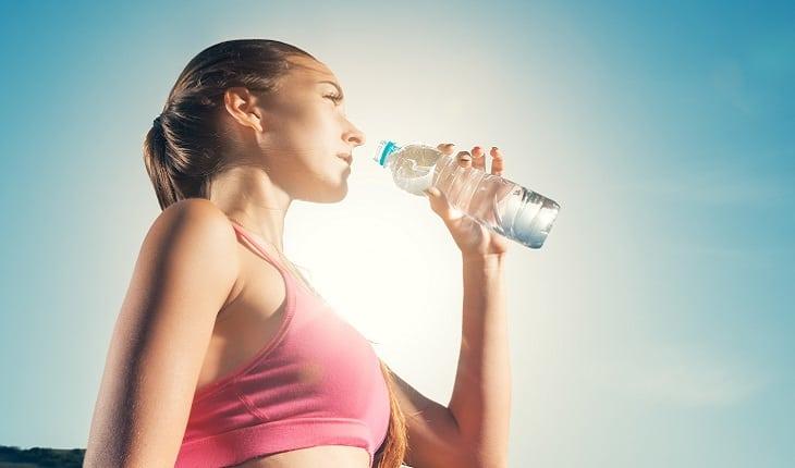 A foto mostra uma mulher bebendo água de uma garrafa