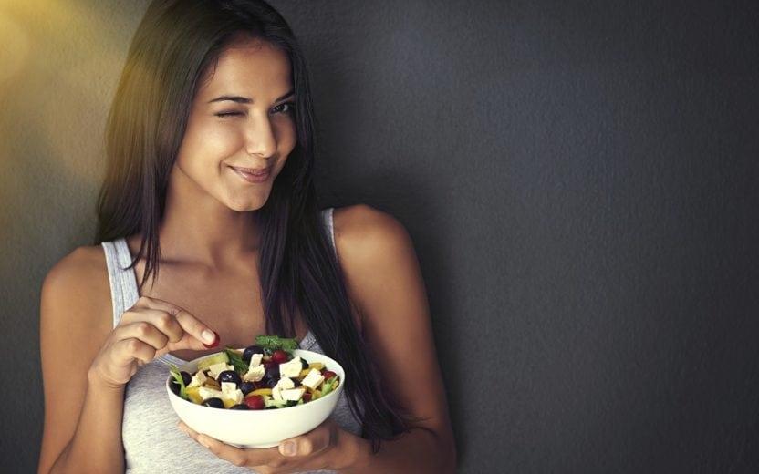 A foto mostra uma mulher comendo salada com queijo. Ela está sorrindo e piscando para a câmera. A foto ilustra o tema do post sobre dicas de alimentação