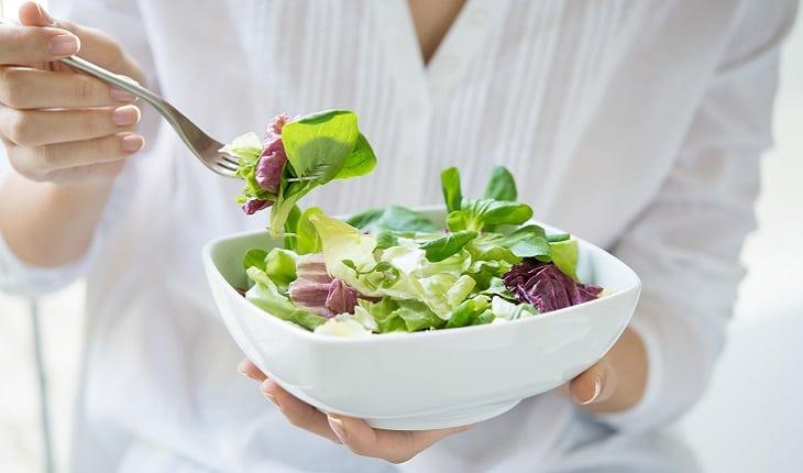 mulher comendo salada em uma tigela