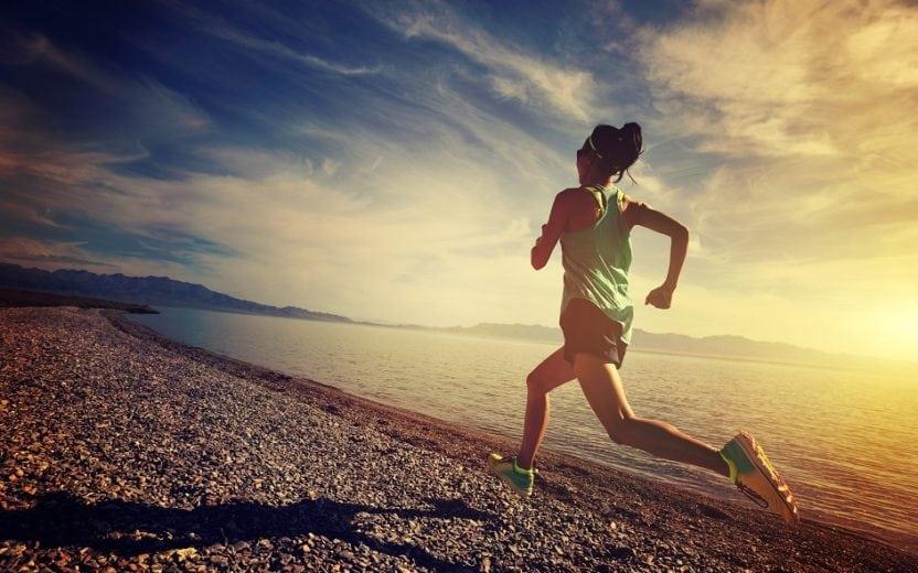 A foto mostra uma mulher correndo na praia, ilustrando o post sobre dicas para começar a correr