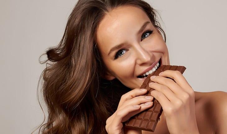 A foto mostra uma mulher mordendo uma barra de chocolate