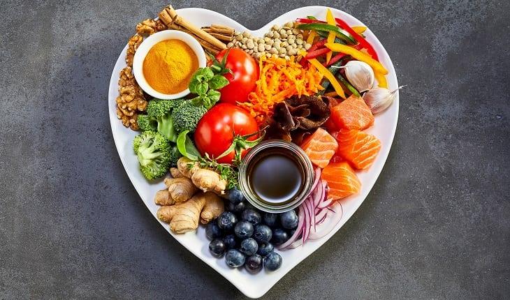 Prevenção do câncer: alimentação balanceada. Na foto, um prato em formato de coração com frutas, verduras, legumes, peixes, dentre outros alimentos.