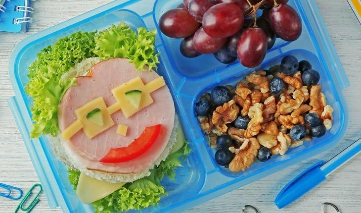 Alimentos nutritivos para as crianças: dicas para as férias de julho. Na foto, uma lancheira com alimentos coloridos e um lanche com carinha.