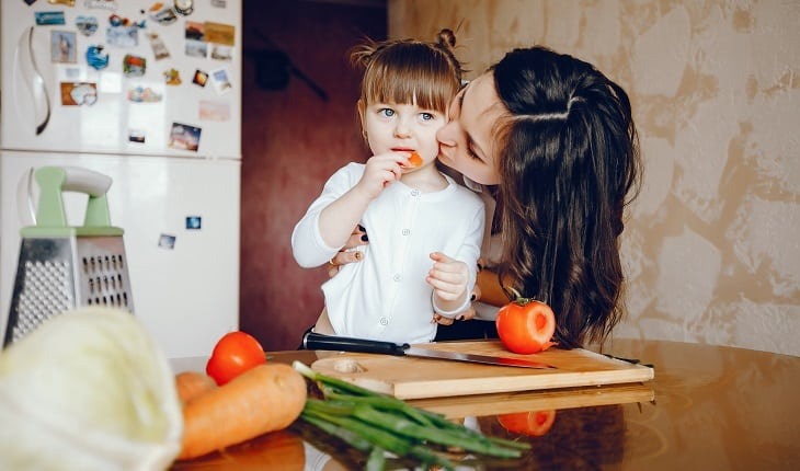 Alimentos nutritivos para as crianças: dicas para as férias de julho. Na foto, uma mãe com a filha cozinhando.