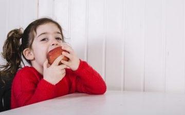 alimentos nutritivos para as crianças. Na foto, uma menina sentada comendo uma maçã