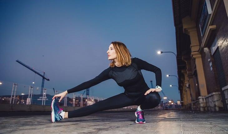 Prevenção do câncer: exercícios físicos. Na foto, uma mulher na rua se alongando para iniciar um exercício físico.